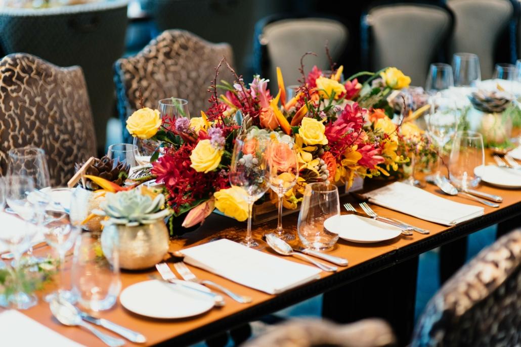 hübsch gedeckter Tisch, mit einem großen Blumengesteck in der Mitte, Photo by CHUTTERSNAP on Unsplash