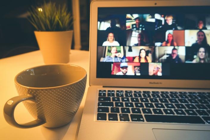 geöffneter Laptop steht auf einem Tisch, daneben eine Tasse. Auf dem Bildschirm sind Gesichter von Menschen erkennbar, die gerade in einer Videokonferenz sind.