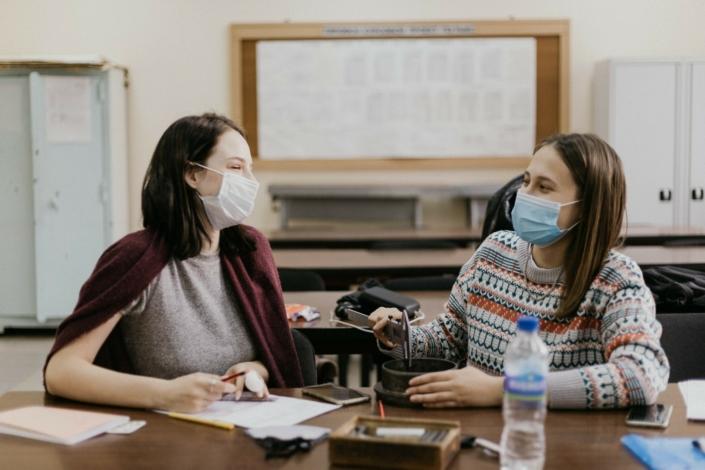 zwei junge Frauen sitzen sich in einer Schule mit Maske gegenüber, sie arbeiten an einer praktischen Aufgabe.