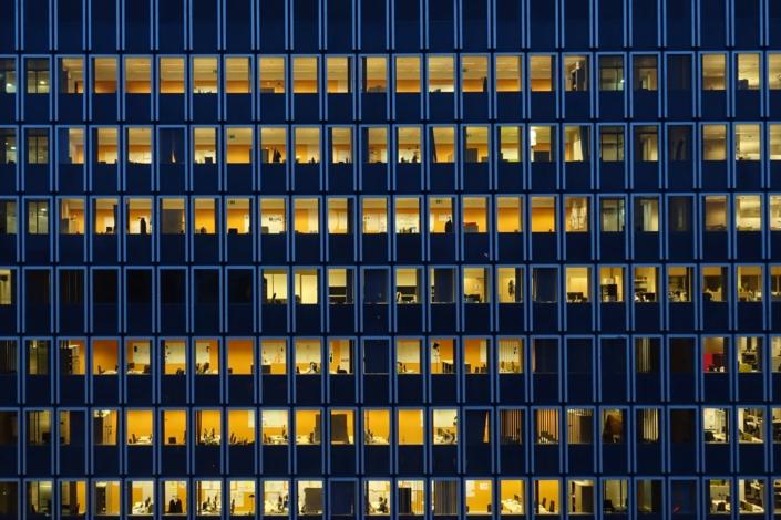 Bürogebäude nach Einsetzen der Dunkelheit, in vielen Büros brennt noch Licht
